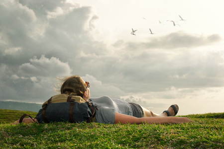 freedom concept: Carefree happy woman traveler with backpack lying on green grass on top of mountain edge cliff enjoying sun and clouds. Hiker think and relaxing after an excursion in the nature.