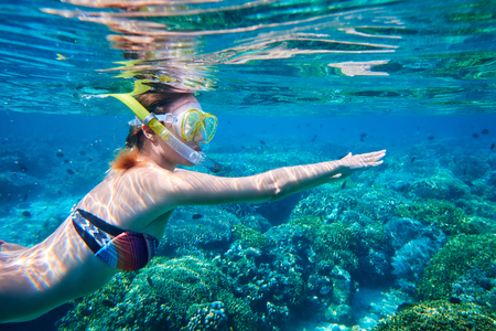 Young woman swimming above the colorful coral reef island Bunaken. Indonesia
