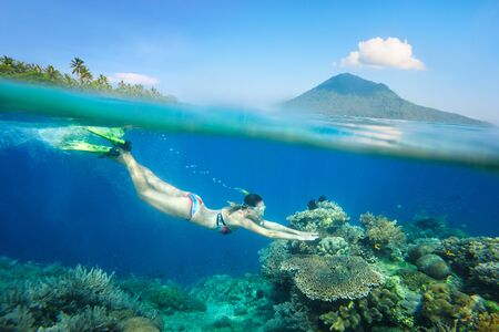 Snorkeling woman over a beautiful coral reef in the background the island of Bunaken, North Sulawesi. Indonesia.