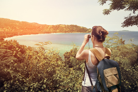 mochila de viaje: Happy woman tourist with backpack enjoying sunny coast view. Traveling along mountains and coast, freedom and active lifestyle concept.