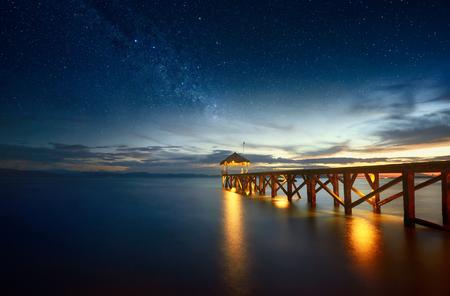空と海に伸びる桟橋の星と美しい夜海の風景。 夏、旅行、休暇、休日のコンセプト - インドネシア ・北スラウェシ島の日没の間の木製桟橋。