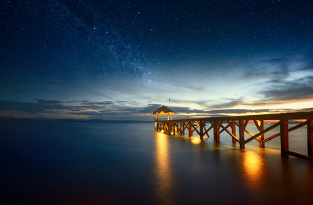 Beautiful night seascape with stars in the sky and pier stretching into the ocean.  Summer, Travel, Vacation and Holiday concept - Wooden pier between sunset in North Sulawesi, Indonesia.