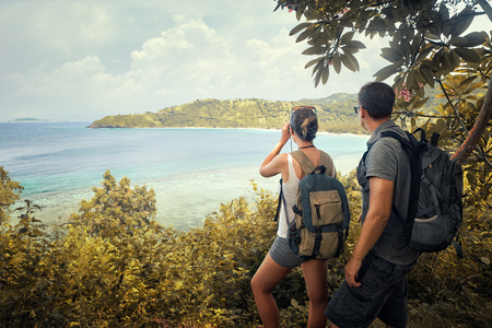 Couple tourists with backpacks enjoying view coast island Lombok on top of a mountain.