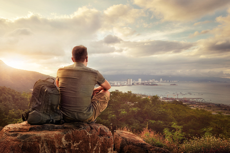 Traveller with backpack sitting on top of mountain enjoying view coast a modern city 