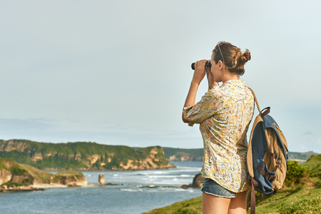 Happy young woman tourist with backpack enjoying sunny coast view on sunrise. Traveling along mountains and coast, freedom and active lifestyle concept.