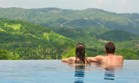 Vue arrière du couple heureux dans la piscine en regardant le paysage de montagne. Voyage, émotion de bonheur, concept de vacances d'été. Banque d'images - 73534114