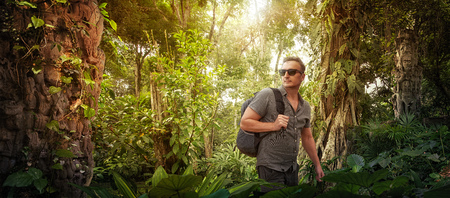 explorer- tourist with backpack studies ancient ruins in the Central America wild jungles.