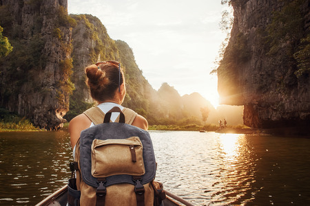 Woman with backpack swims on boat among karst mountains to meet her friends. Tam Coc,  North of Vietnam.Travel and active lifestyle, summer holiday concept.