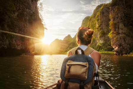 Happy woman with backpack traveling by boat enjoying sunset among of karst mountains in the North of Vietnam. Travel and active lifestyle, summer holiday concept.