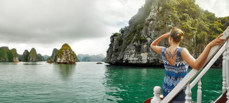 attractive woman in a dress is traveling by boat in Halong Bay. Vietnam. Travel to Asia, happiness emotion, summer holiday concept