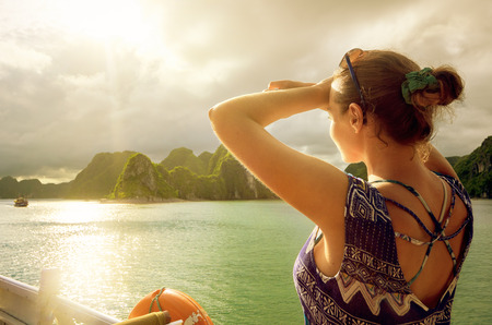 Woman traveler on the boat, enjoying the view of the island at sunset in Halong Bay, Vietnam.