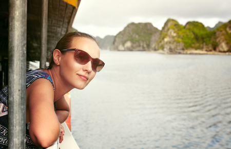 pretty woman traveler sails on a ship among the beautiful islands in Halong Bay, Vietnam photo