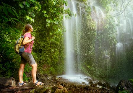 Reizigersvrouw die met rugzak de waterval in wildernissen in zonlicht bekijken. Verken langs de bergen en het regenwoud, vrijheid en actief levensstijlconcept.