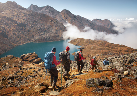 Group of tourists with backpacks descends down mountain trail to lake during a hike in the national park Lantang, Nepal. Beautiful inspirational landscape, trekking and activity.