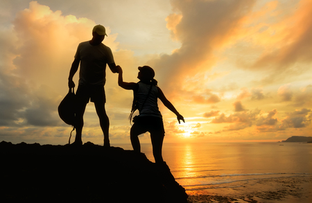 Male and female hikers climbing up mountain cliff looking at beautiful sunset  and one of them giving helping hand . People helping and, team work concept. Stock Photo