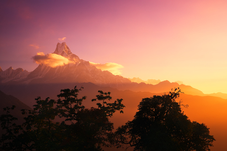 Scenic landscape with a peak Machapuchare, Nepal on sunrise. Natural mountain background. Stock Photo