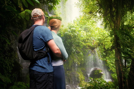 Beautiful young couple enjoying the company of each other in jungle looking view of the waterfall. Island Lombok, Indonesia. Enjoy each others company on travel. Stock Photo