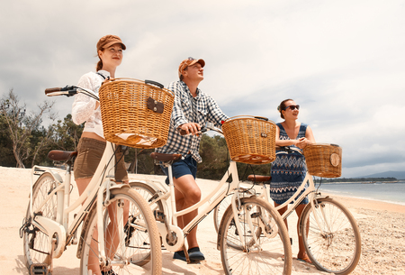 Enjoy each other's company on travel. Front view of young people cycling together while spending carefree time outdoors in holiday. Banque d'images - 96265261