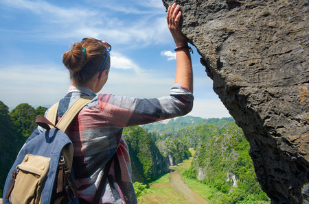 Woman with backpack on top of the mountain enjoying river and valley view. Ninh Binh, Vietnam. Mountains landscape, travel to Asia, happiness emotion, summer hike concept.