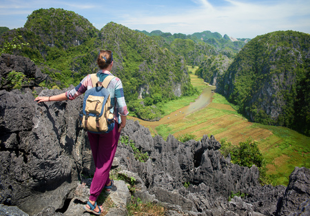 Woman with backpack on view point enjoying river and valley view. Ninh Binh, Vietnam. Mountains landscape, travel to Asia, happiness emotion, summer hike concept.