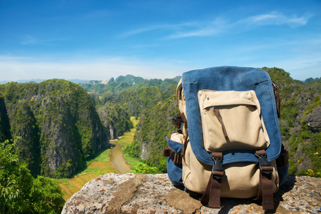 Travel backpack closeup. View on front tourist traveler bag on background mountains and valley in sunny day. Stock Photo