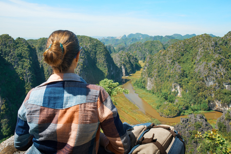 Young woman with backpack sitting on top of the mountain and enjoying river and valley view. Ninh Binh, Vietnam. Mountains landscape, travel to Asia, happiness emotion, summer hike concept.