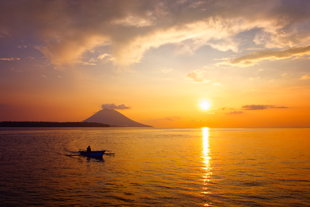 Traditional Indonesian boat in the beautiful golden sunset against the background of the Manado Tua volcano. North Sulawesi, Indonesia
