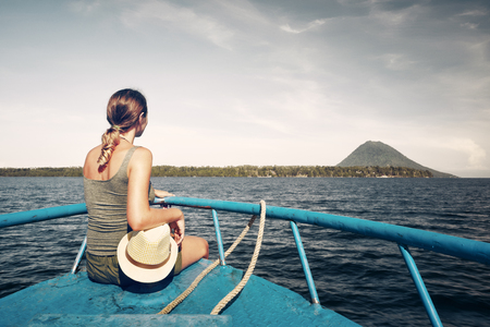 Traveler woman sit on boat looking to a island Bunaken and volcano Manado Tua. North Sulawesi, Indonesia. Banque d'images - 98190714