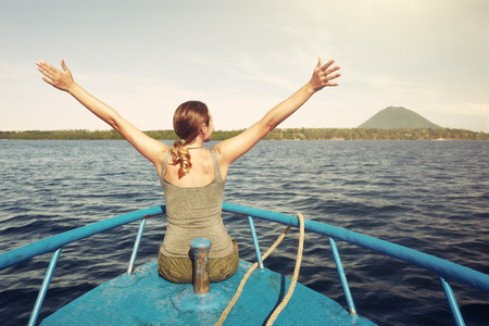 Happy woman with raised hands sit on boat enjoying at the coast and volcano Manado Tua. North Sulawesi, Indonesia. Travel and discovery,  happiness emotion, summer holiday concept Stock Photo