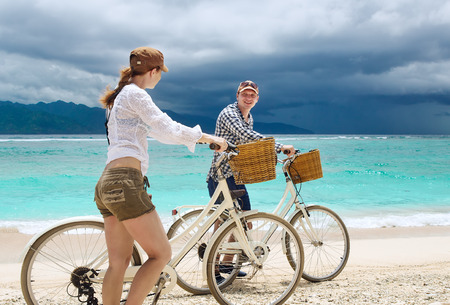Cheerful young people talking and smile while walking near their bicycles on the beach.