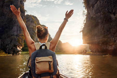 Just having fun in travel. Joyful woman traveler with backpack travels a river against a background of karst mountains. Ninh Binh province, Vietnam.