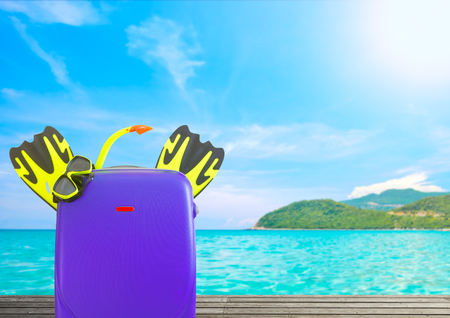 Concept of summer travelling with suitcase and accessories for snorkel. Focus on the foreground on background tropical beach  Stock Photo