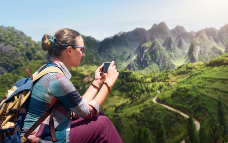 Woman traveler with smartphone is exploring a picturesque karst mountain plateau in the North Vietnam. Traveling and exploration along mountains, freedom and active lifestyle concept. Stock Photo