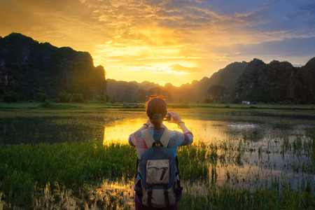 Woman with backpack travels and photographs a beautiful sunset over the mountains in the countryside in Vietnam.