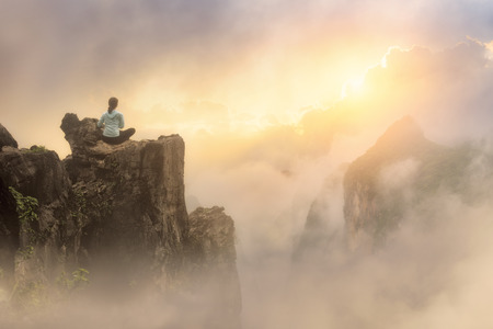 Traveler sitting on cliff enjoying view on mountains and clouds to sunrise.North Vietnam Mountains landscape, travel to Asia, summer holiday concept