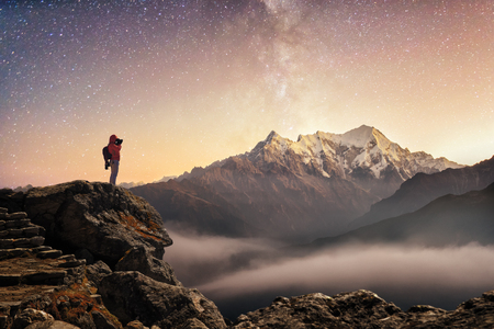 Photographer traveler who take a picture of starry sky enjoying sunrise on peak of over snowy mountains in the Himalayas, Langtang, Nepal. Night colorful landscape. Starry sky with mountains at winter.