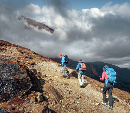 Group of tourists with backpacks get up mountain trail during a hike in the national park Lantang, Nepal. Beautiful inspirational landscape, trekking and activity. Stock Photo