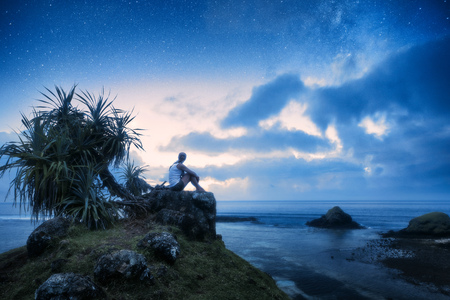 A lonely woman sits on the seashore and looks at the starry sky Banque d'images - 100809801
