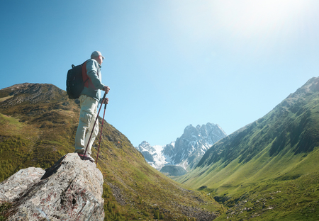 Hiker with Backpack and trekking sticks look view of the Chauhi mountain range in Georgia (country). Beautiful inspirational landscape, trekking and activity. Travel sport lifestyle concept