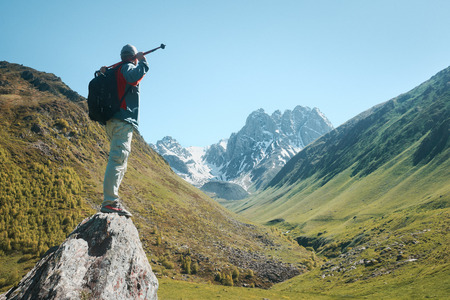 Man with Backpack and trekking sticks look view of the Chauhi mountain range in Georgia (country). Beautiful inspirational landscape, trekking and activity. Travel sport lifestyle concept
