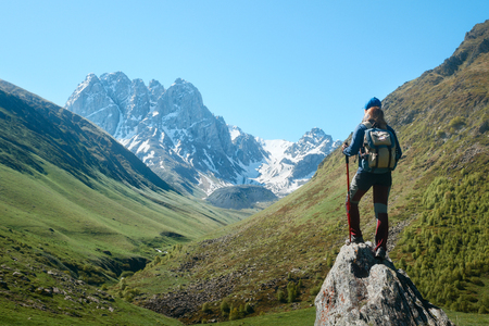 Hiker with Backpack and trekking sticks look view of the Chauhi mountain range in Georgia (country). Beautiful inspirational landscape, trekking and activity. Travel sport lifestyle concept Stock Photo