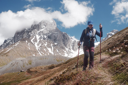 Happy hiker with trekking sticks walks and enjoys on the mountain trail. Mountain range Chauhi, Georgia (country). Beautiful inspirational landscape, trekking and activity. Travel sport lifestyle concept