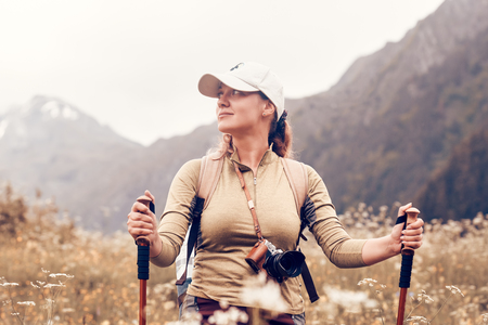 Happy tourist with a backpack and trekking sticks goes and enjoys nature. Traveling along the mountains and fields, freedom and active lifestyle concept.