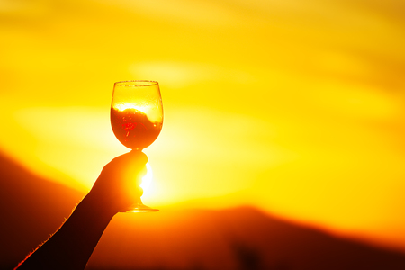 Woman holding glass of wine on the background of beautiful sunset in Georgia(country) Banque d'images - 116122998