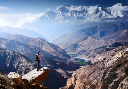 Hiker with Backpack and trekking sticks looks at the beautiful mountain canyon in Upper Mustang. Nepal Beautiful inspirational landscape, trekking and activity. Travel sport lifestyle concept Stock Photo