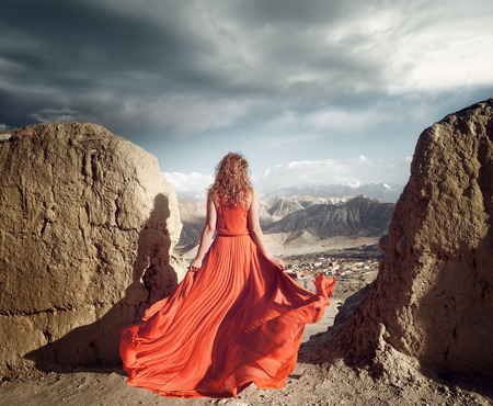 Woman in long red dress on the edge of a cliff in the mountains  looking to sunny valley. 