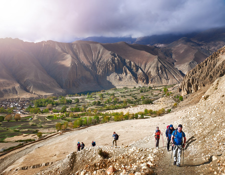 Group of tourists with backpacks rises down mountain trail during a hike in the Upper Mustang, Nepal. Beautiful inspirational landscape, trekking and activity.