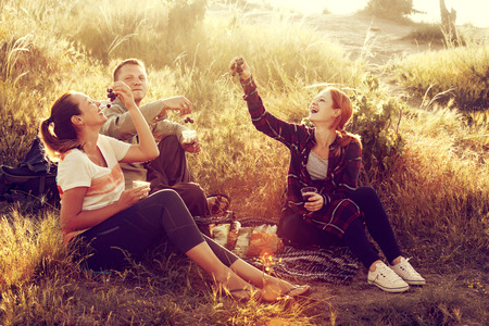 Happy friends having fun outdoors. Young people enjoying time together at countryside during sunset. Fun, joy, leisure concept.