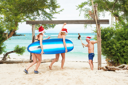 Cheerful company of young people in Santa hats having fun on the beach.