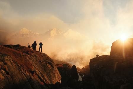 Group tourists resting high in mountains of Himalayas watching the sunset. Beautiful inspirational landscape, trekking and activity. Stock Photo